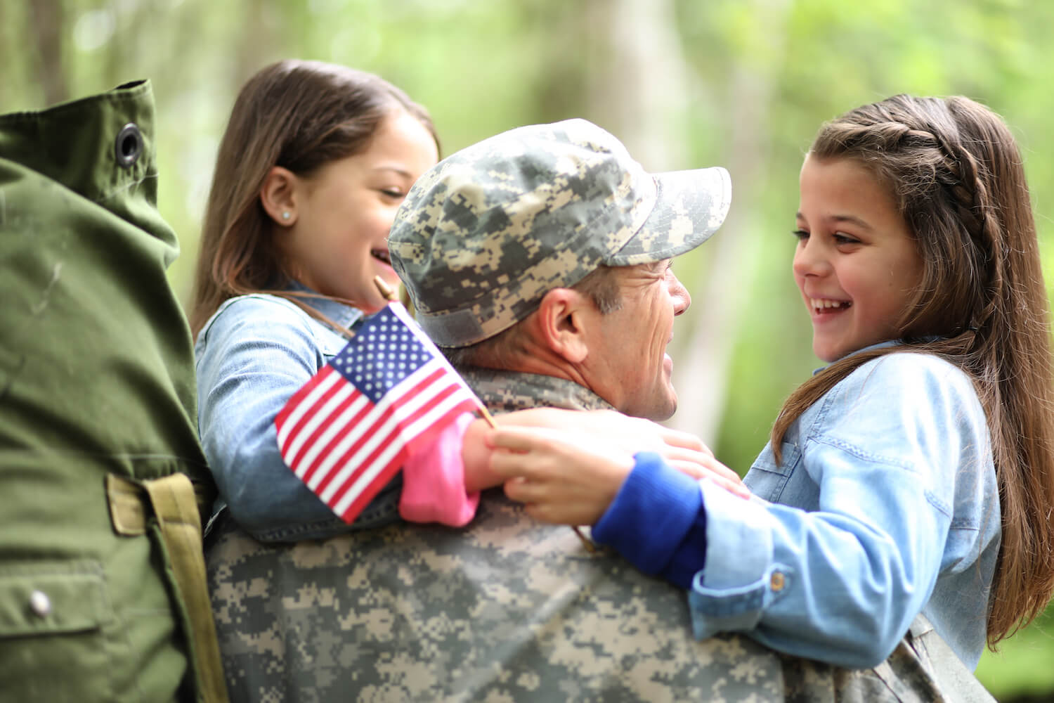 Family welcomes home a USA army soldier. The children excitedly hug father holding American flags.