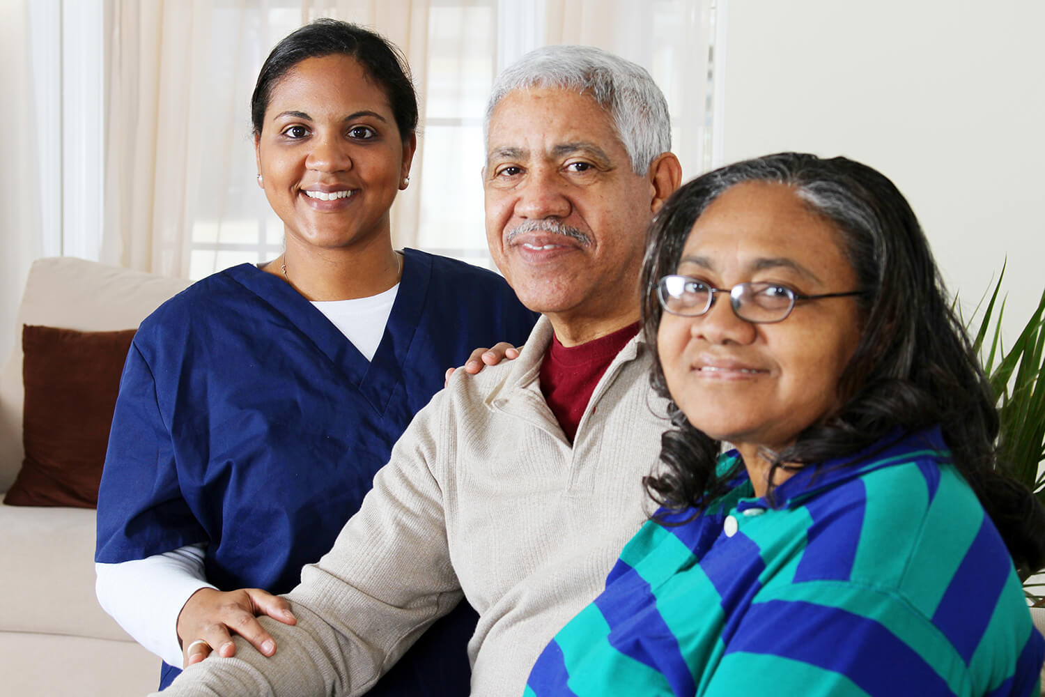 Older man in grey sweater with maroon under shirt sits next to lady in blue and green stiped shirt with glasses while nurse in dark blue scrubs stands behind man's shoulder (all smiling)