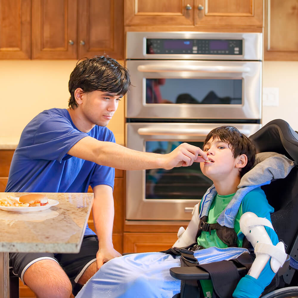 brother in blue shirt feeding weelchair bound younger brother in green and blue shirt in contemporary kitchen with double oven in the background, wood cabinets and granite countertop