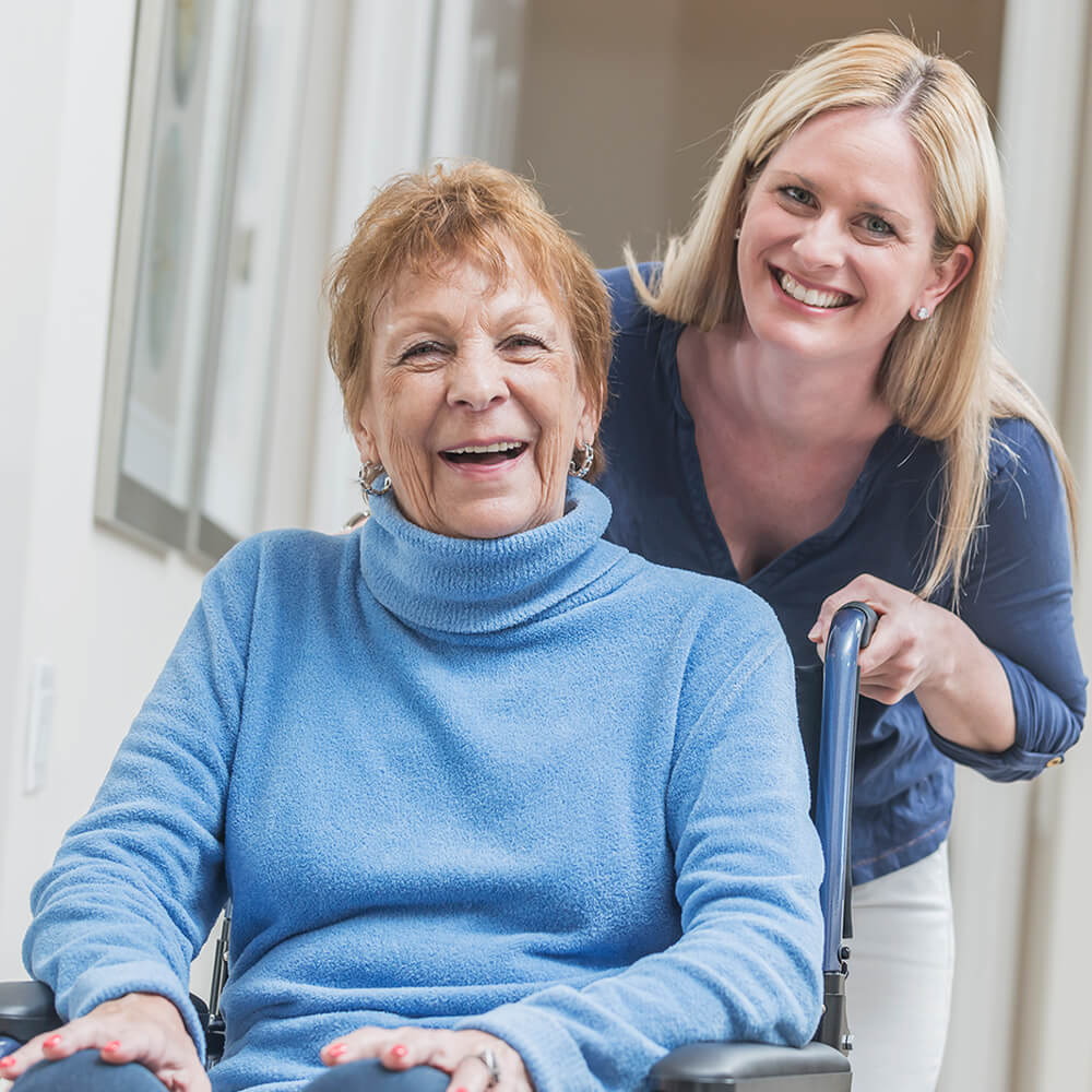 elderly lady in wheelchair wearing blue long sleeve turtleneck sweater with contentedly happy smile (possibly laughing) with younger lady leaning into the picture wearing darker blue V-neck shirt smiling for the picture.
